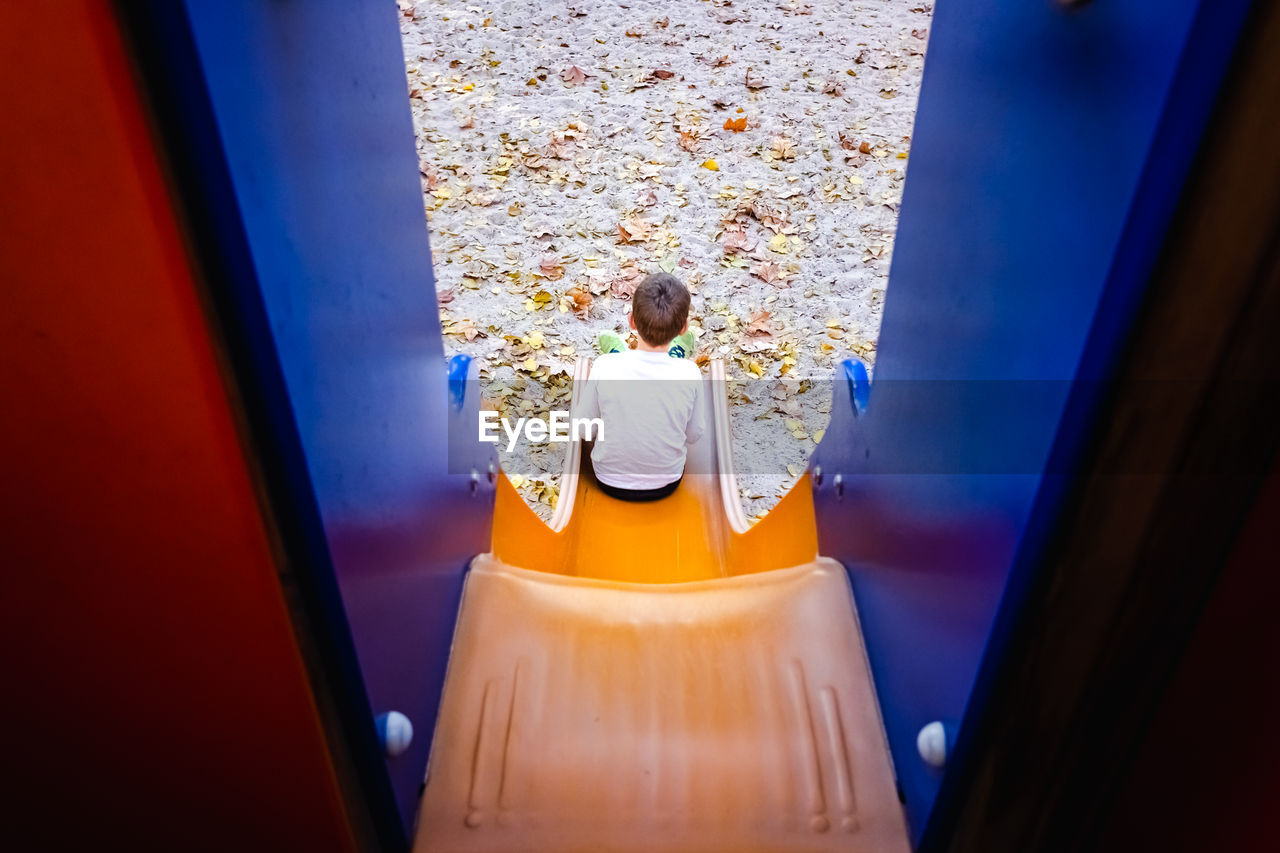 Rear view of boy sitting on slide in playground