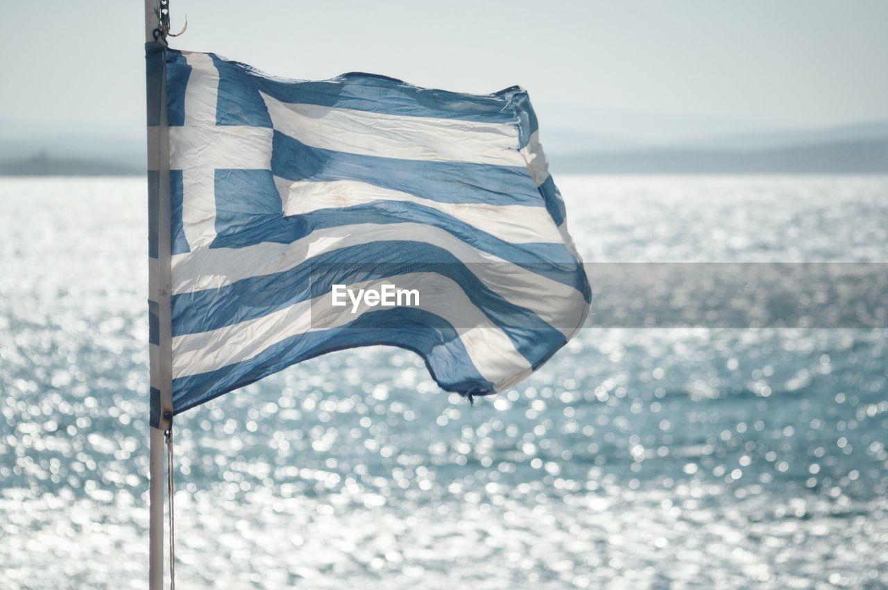 CLOSE-UP OF FLAGS AGAINST SEA