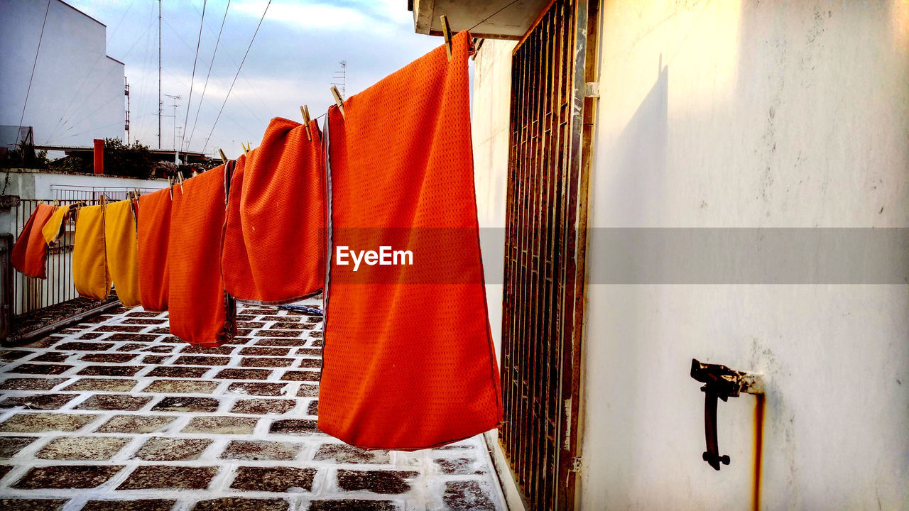 hanging, textile, laundry, no people, architecture, clothing, built structure, drying, building exterior, day, wall, building, wall - building feature, clothesline, nature, cleaning, outdoors, in a row, residential district, red, clean