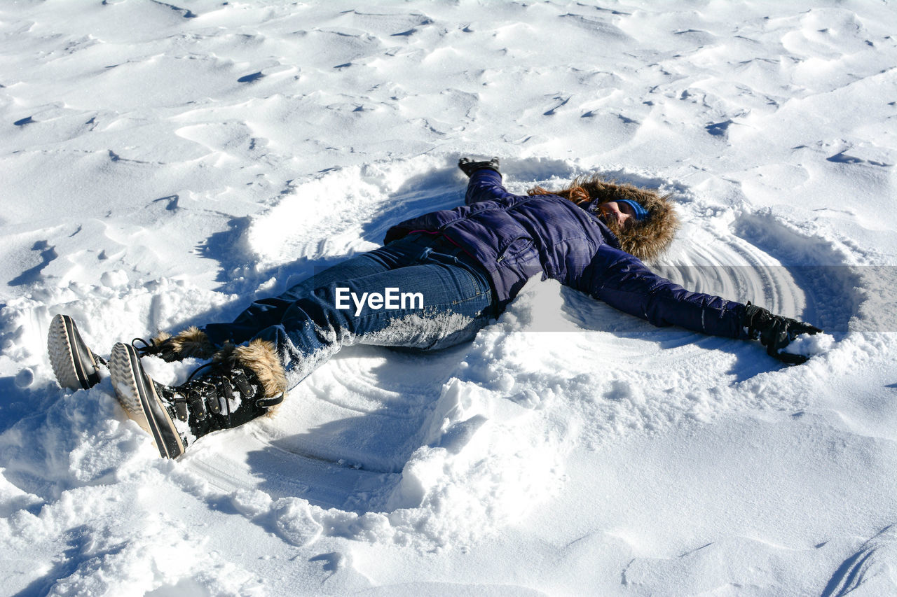 snow, cold temperature, winter, one person, lying down, leisure activity, nature, full length, field, day, high angle view, child, clothing, real people, childhood, lifestyles, sunlight, vacations, warm clothing, outdoors, ski-wear