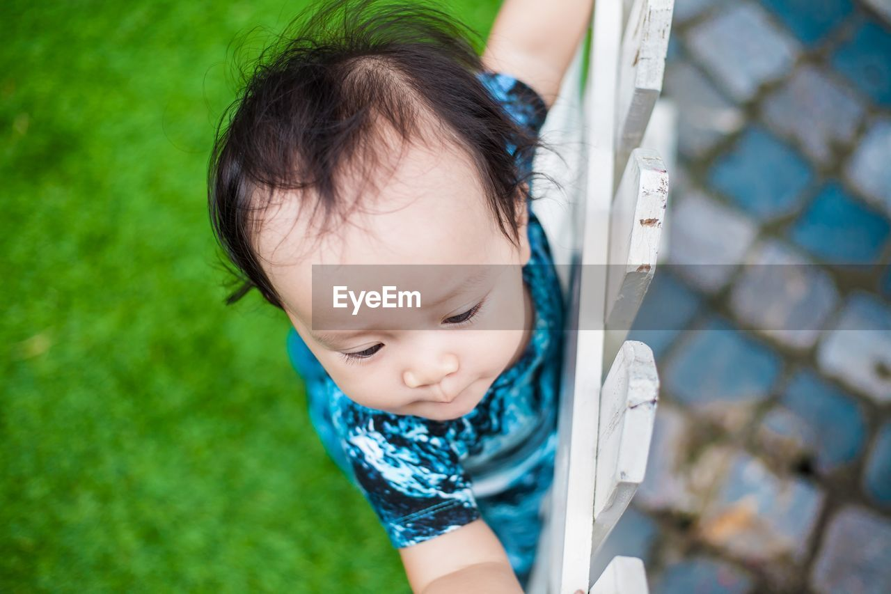 Close-up of baby girl standing on fence