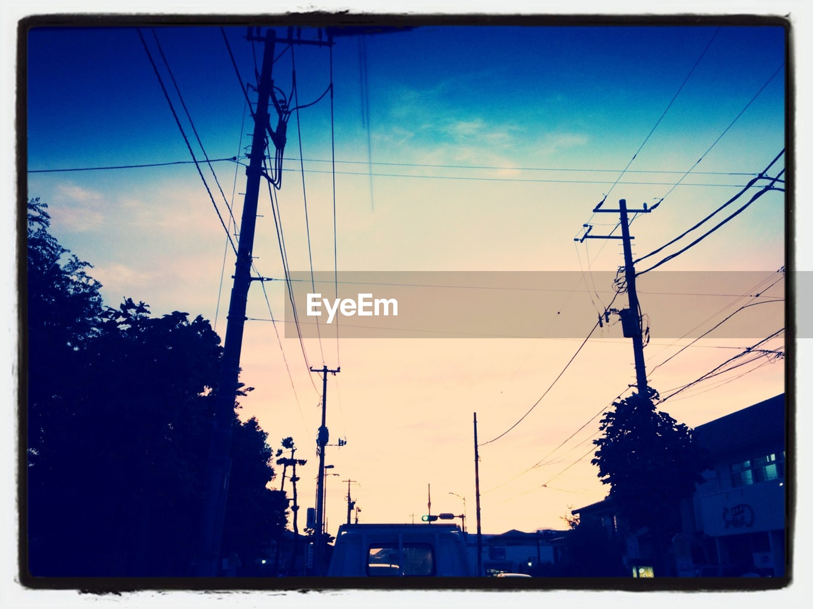 power line, electricity pylon, power supply, electricity, cable, building exterior, silhouette, transfer print, sky, built structure, low angle view, power cable, architecture, sunset, fuel and power generation, auto post production filter, connection, technology, car, street light
