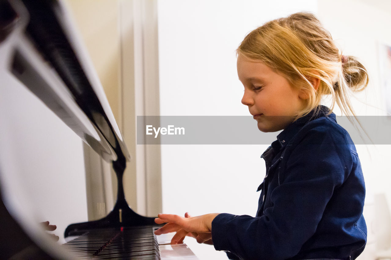 Profile view of girl playing piano