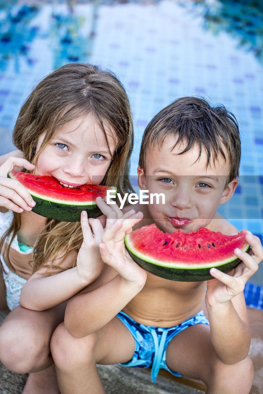 Cute Siblings Having Watermelon Against Swimming Pool