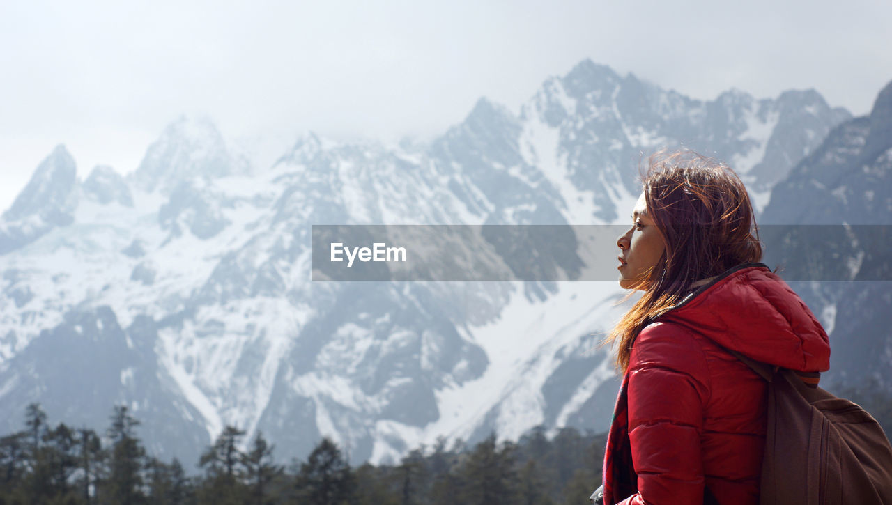 Side view of woman looking away against snowcapped mountains