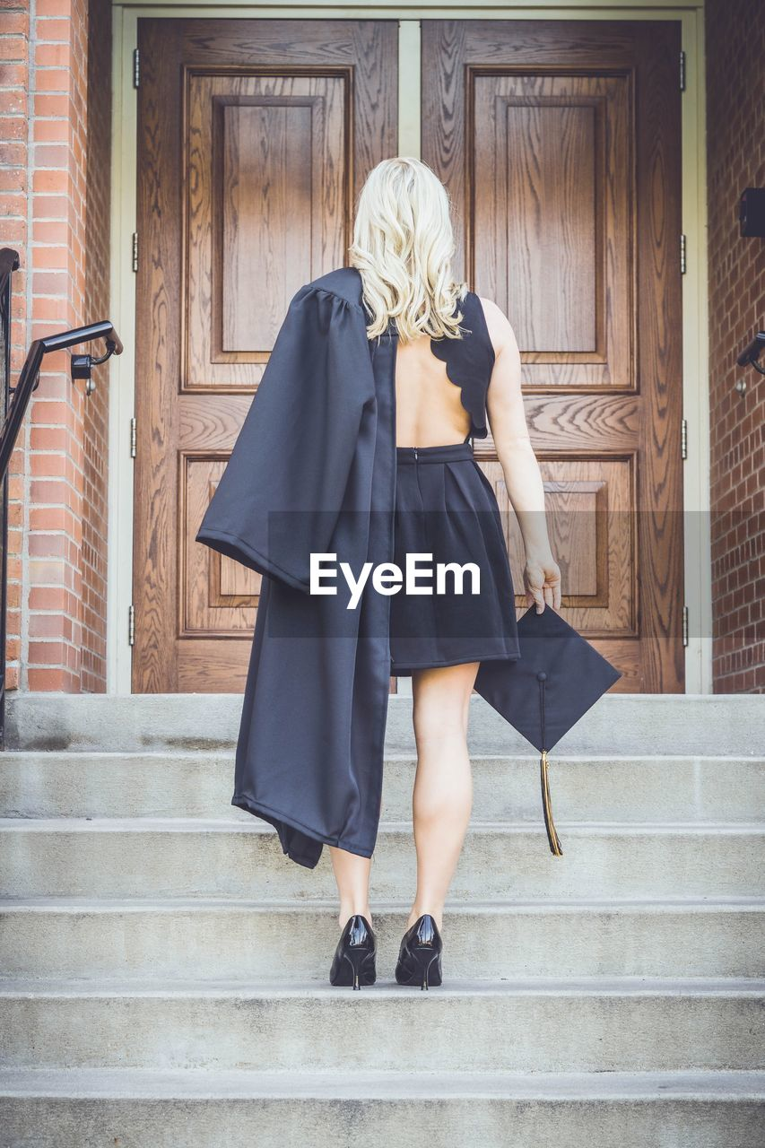Rear view of woman holding mortarboard while standing on steps