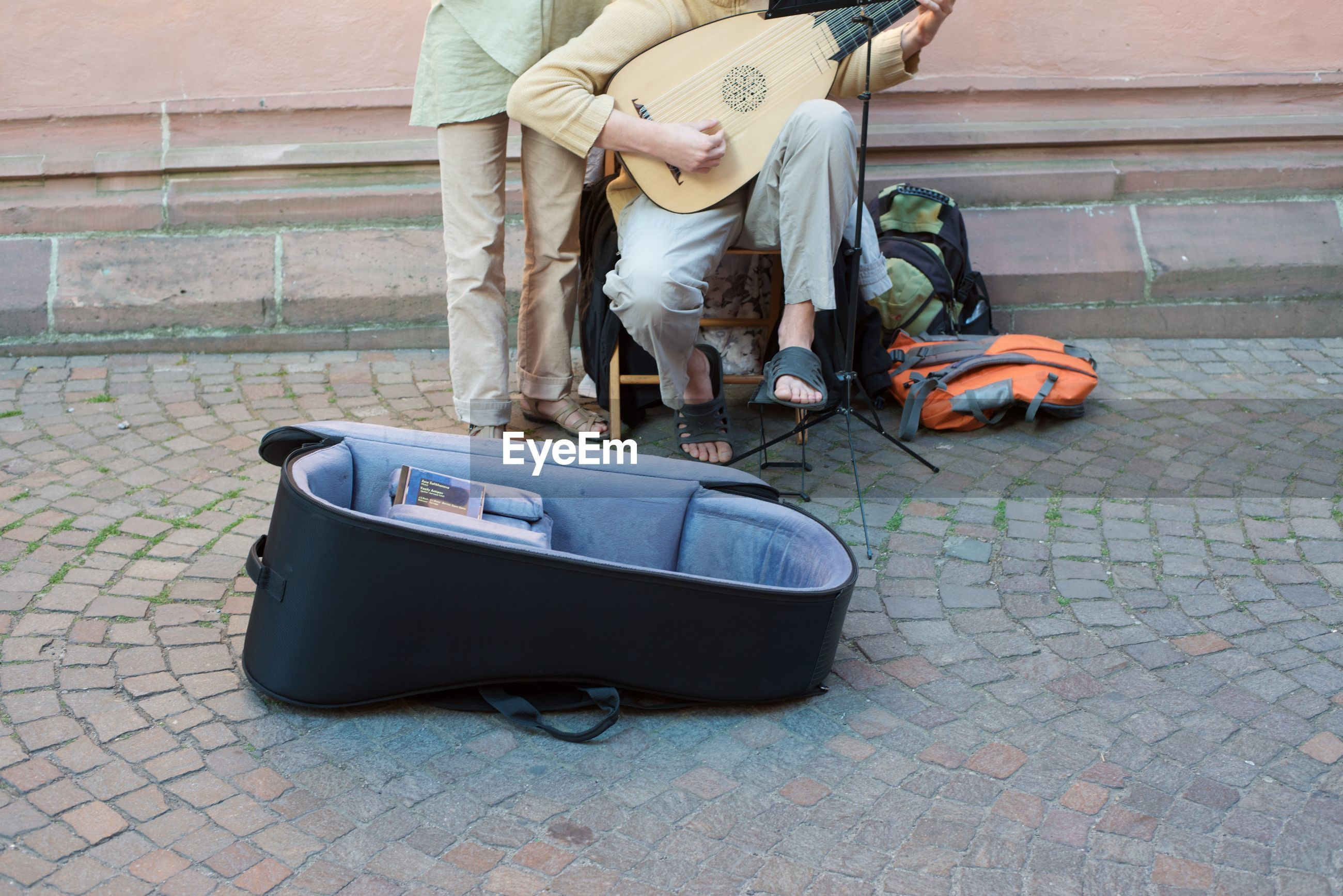 Low section of man with friend playing musical instrument on street