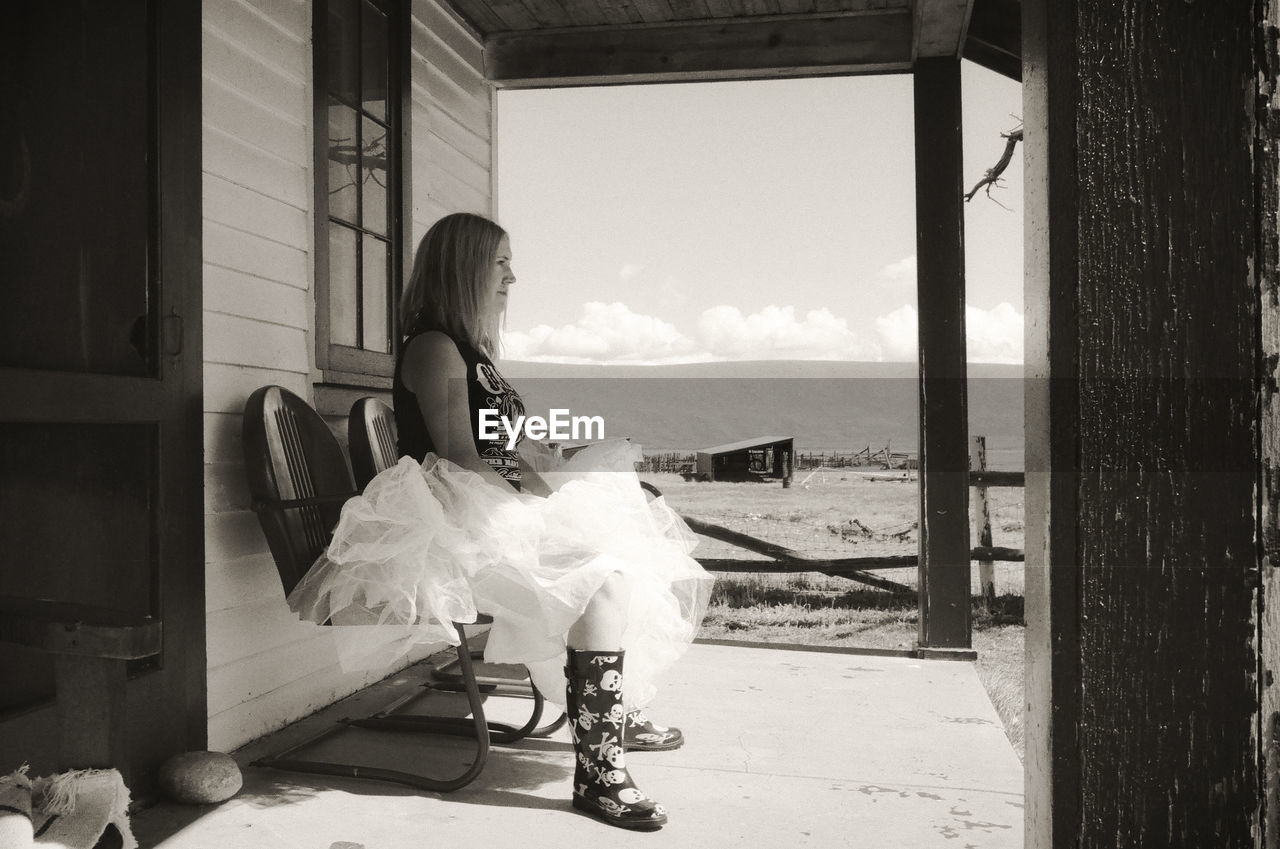 Side view of woman sitting on chair at porch