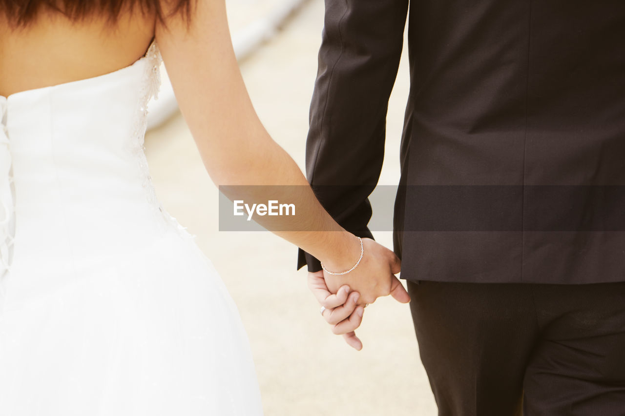 two people, midsection, love, wedding, wedding dress, bride, adult, men, women, newlywed, positive emotion, togetherness, real people, bonding, life events, bridegroom, celebration, married, event, ceremony, couple - relationship, hand, wedding ceremony