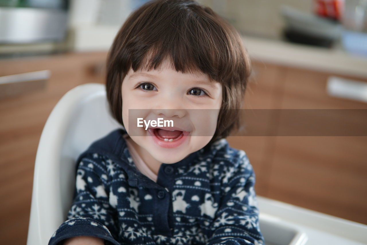 Close-up of happy baby sitting on highchair at home