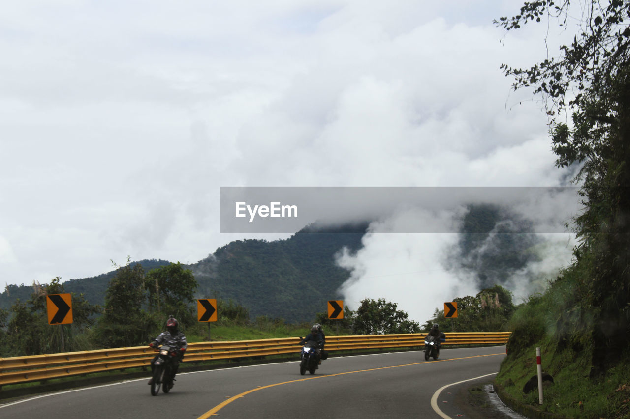 People Riding Motorcycle On Street Against Cloudy Sky