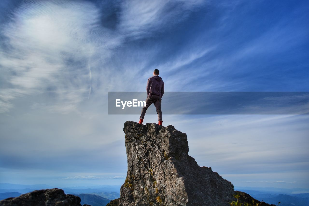 cloud - sky, rock, one person, rock - object, solid, sky, leisure activity, standing, full length, lifestyles, real people, beauty in nature, vacations, nature, low angle view, trip, mountain, holiday, men, outdoors, conquering adversity