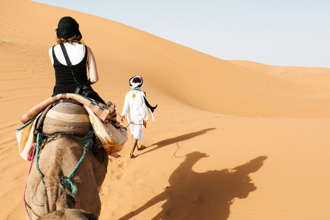 Rear View Of Woman Sitting On Camel At Desert