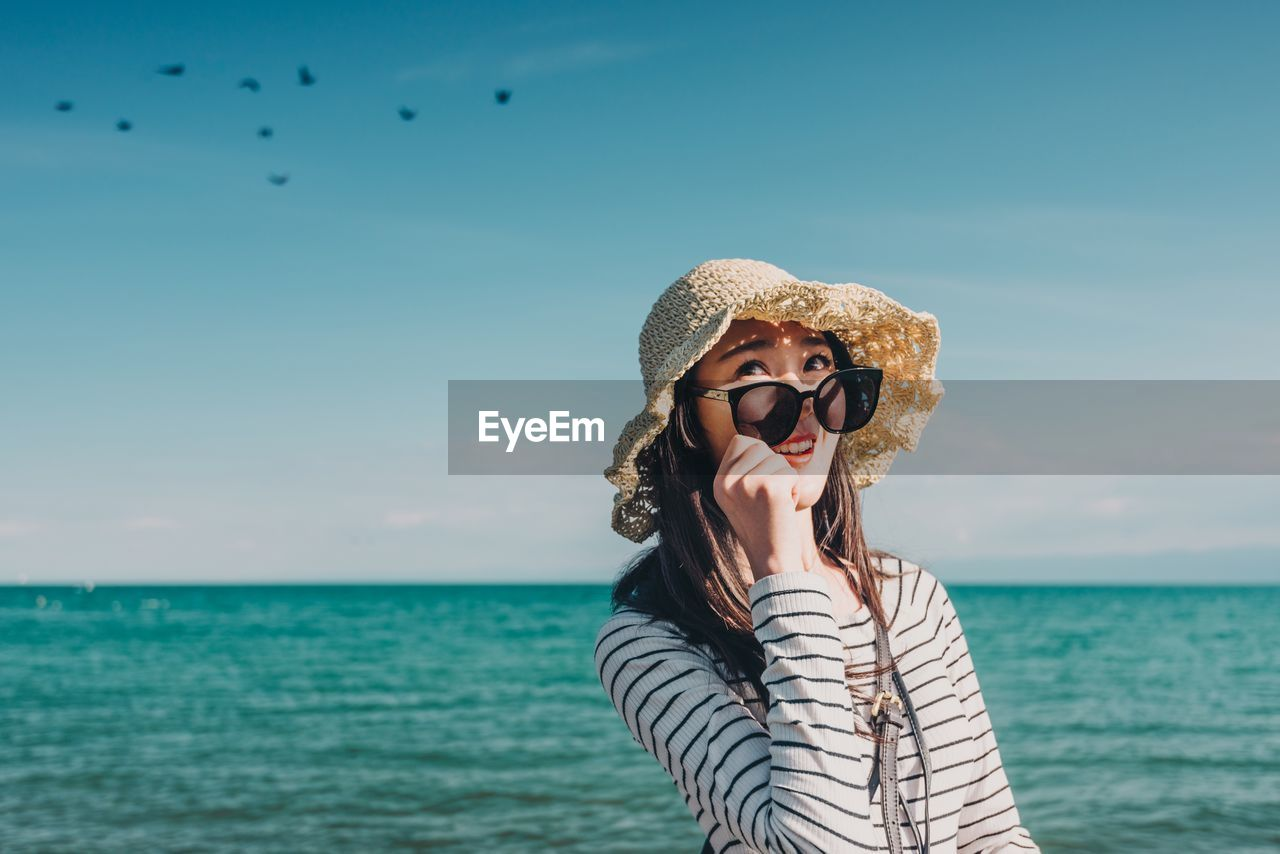 Young Woman In Hat And Sunglasses Standing Against Sea