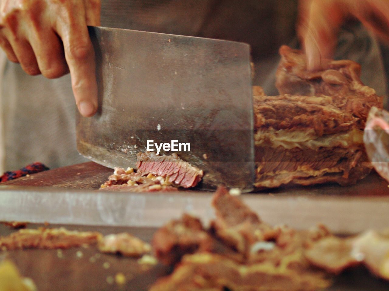 Cropped Image Of Butcher Cutting Meat