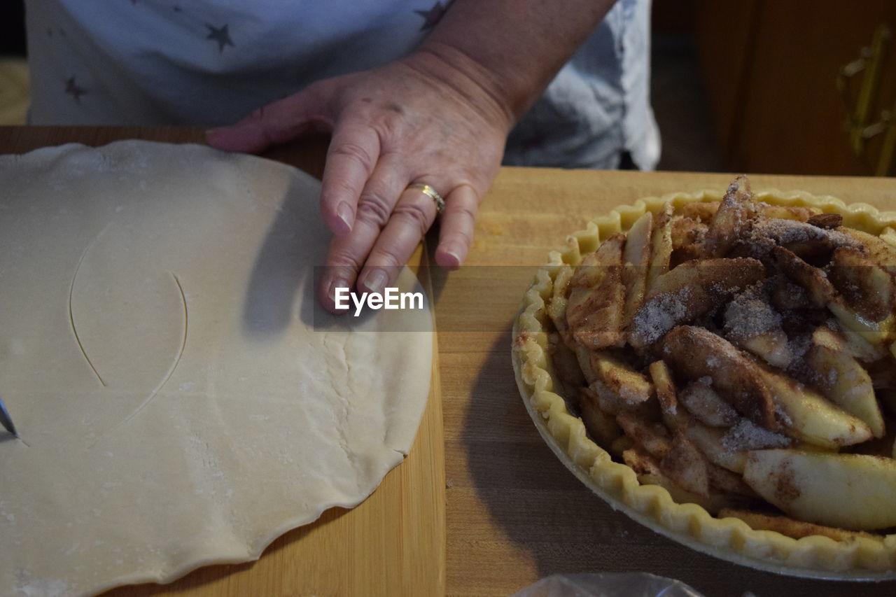 Cropped Image Of Hand Preparing Apple Pie