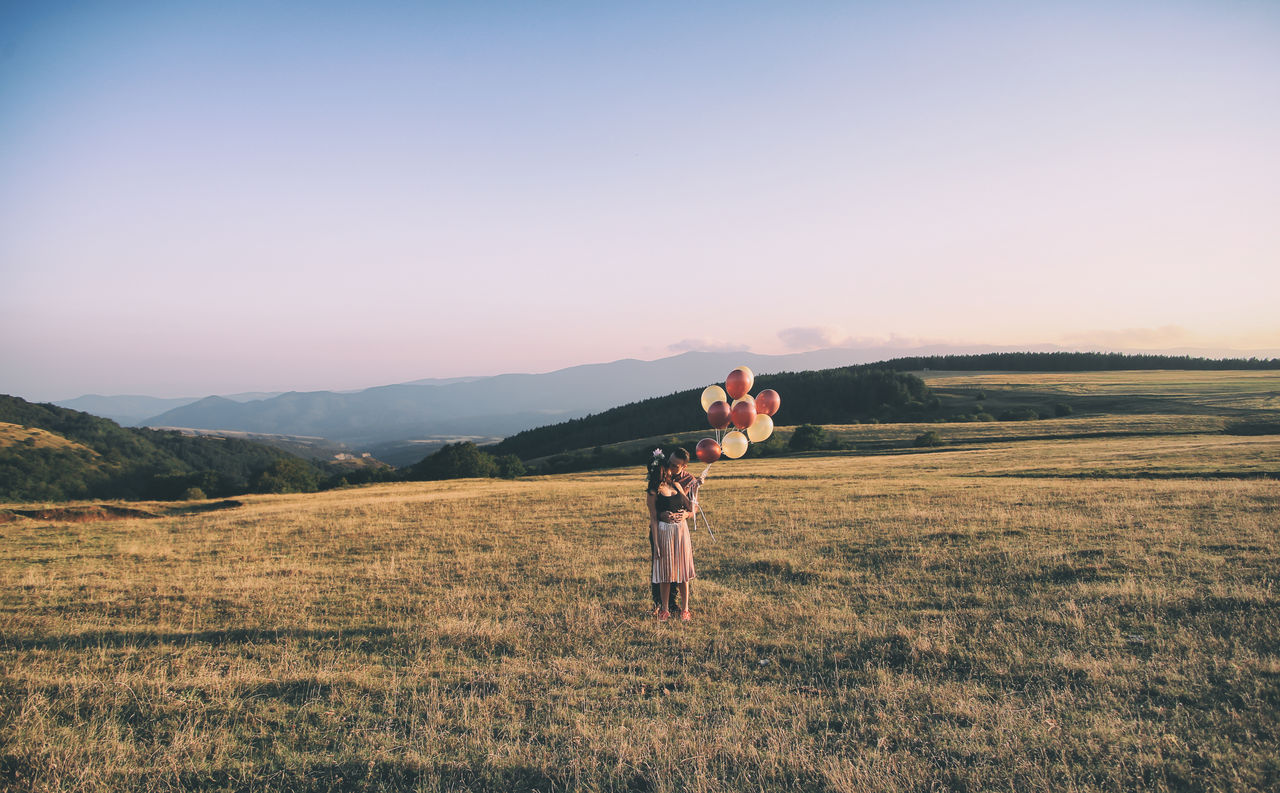 Young Couple With Balloon Kissing On Field Against Sky During Sunset