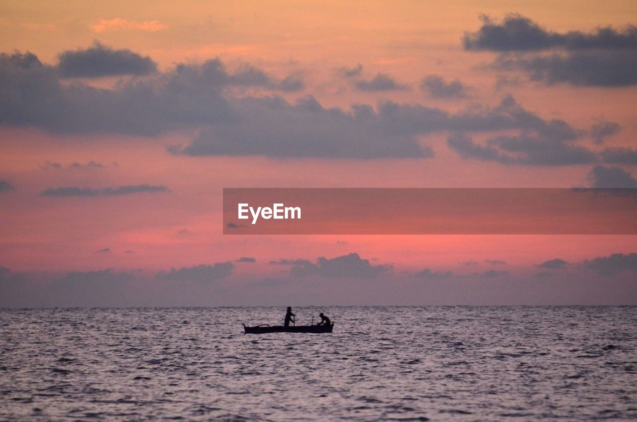 Silhouette boat in calm sea against sky