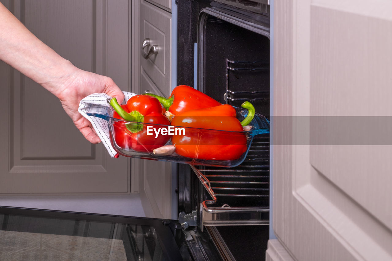MAN HOLDING RED CHILI PEPPERS AT HOME