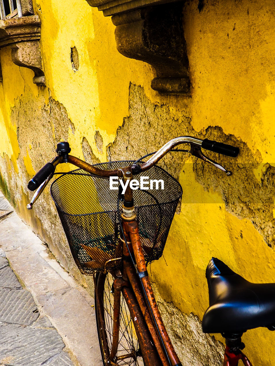 bicycle, land vehicle, yellow, wall - building feature, architecture, mode of transportation, transportation, built structure, stationary, wall, no people, building exterior, day, handlebar, basket, metal, parking, street, bicycle basket, outdoors