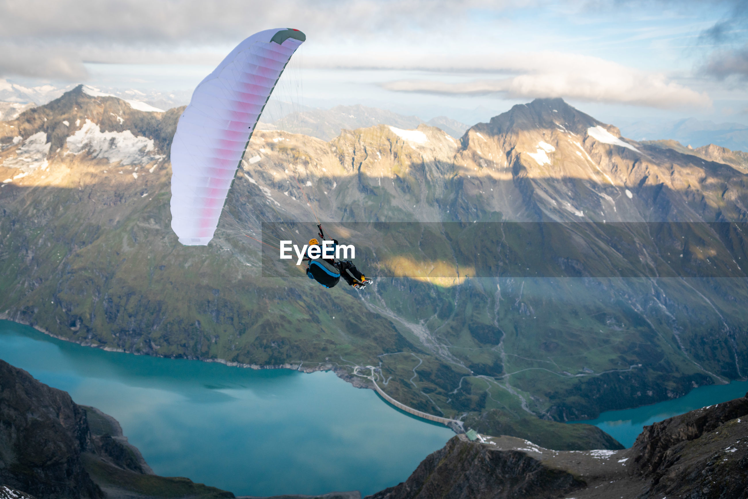 Man paragliding over mountains against sky