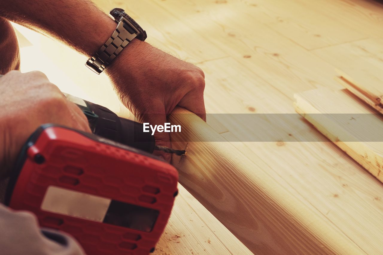Cropped image of man drilling plank with power tool