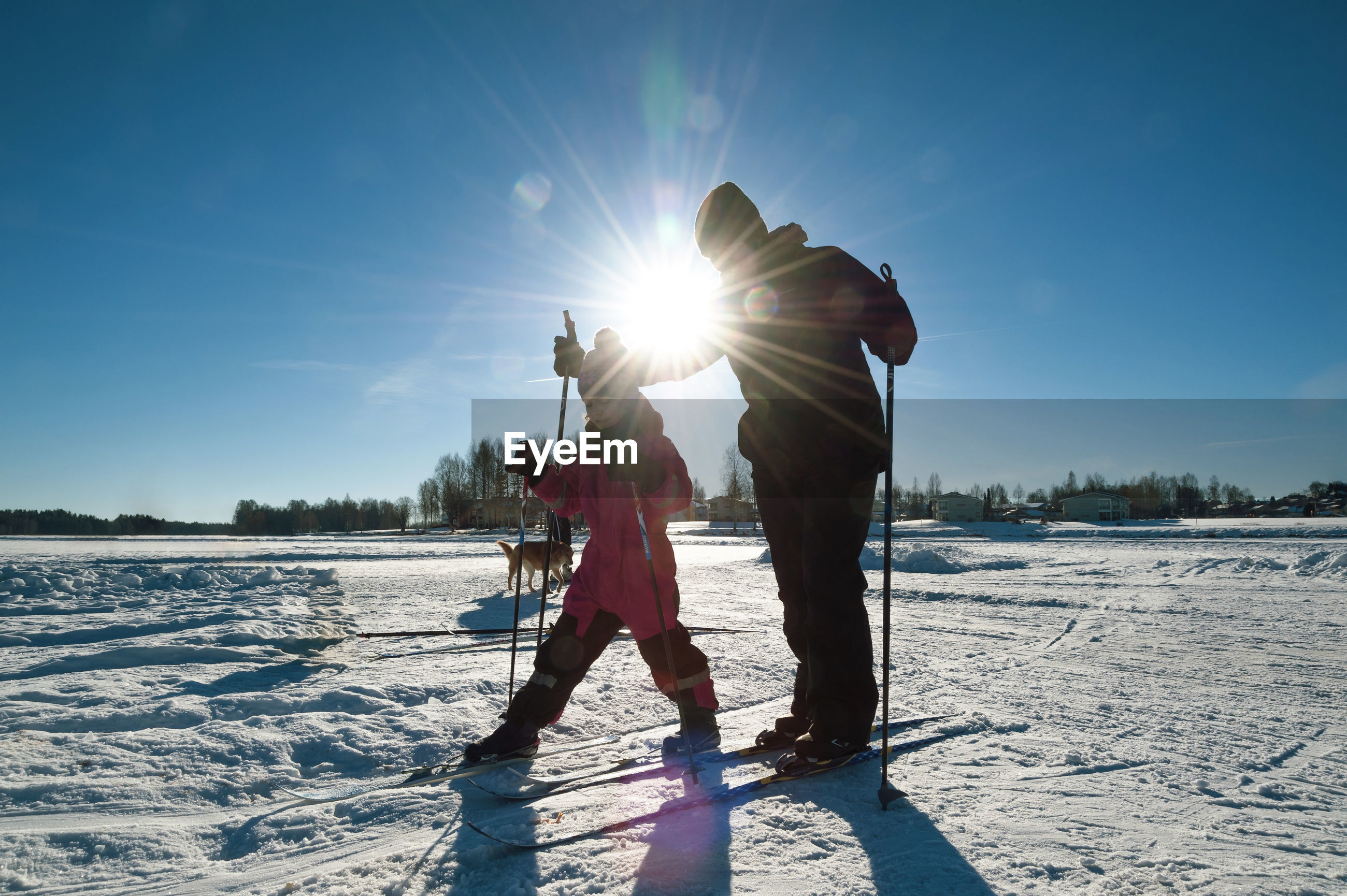 Mother assisting daughter during ski against bright sky