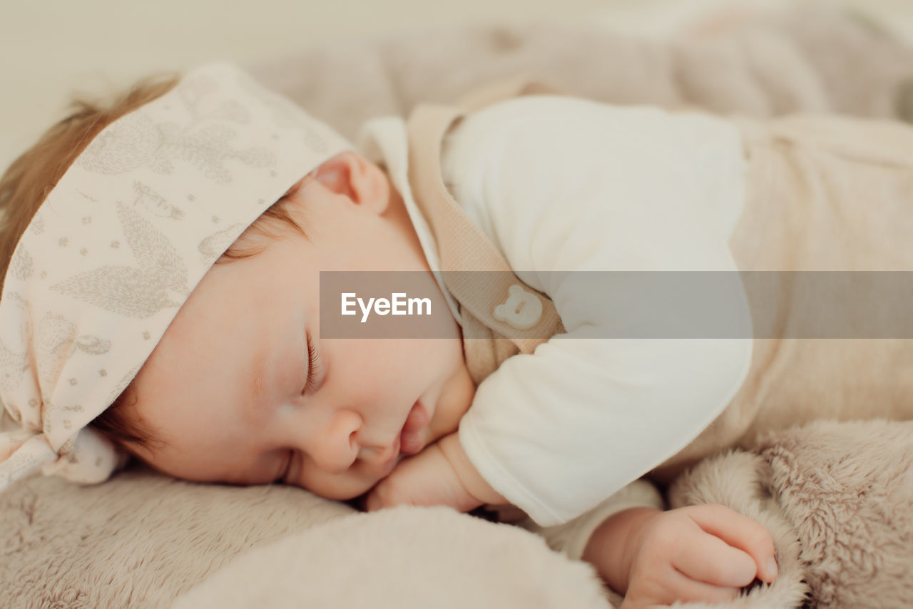child, bed, lying down, childhood, furniture, sleeping, baby, relaxation, young, eyes closed, real people, one person, innocence, indoors, babyhood, cute, resting, comfortable, napping