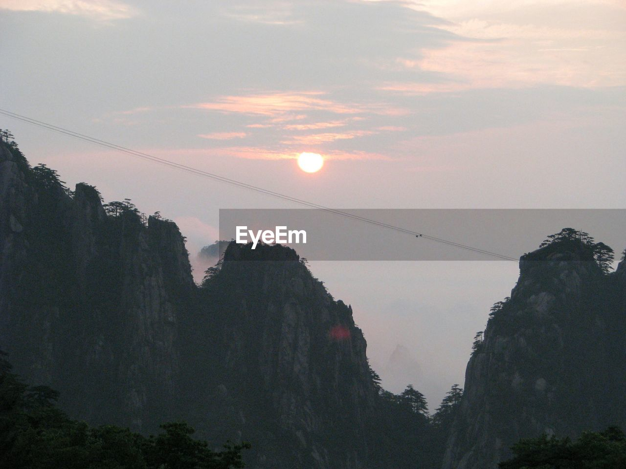 Scenic view of huangshan mountain range against sky at sunset