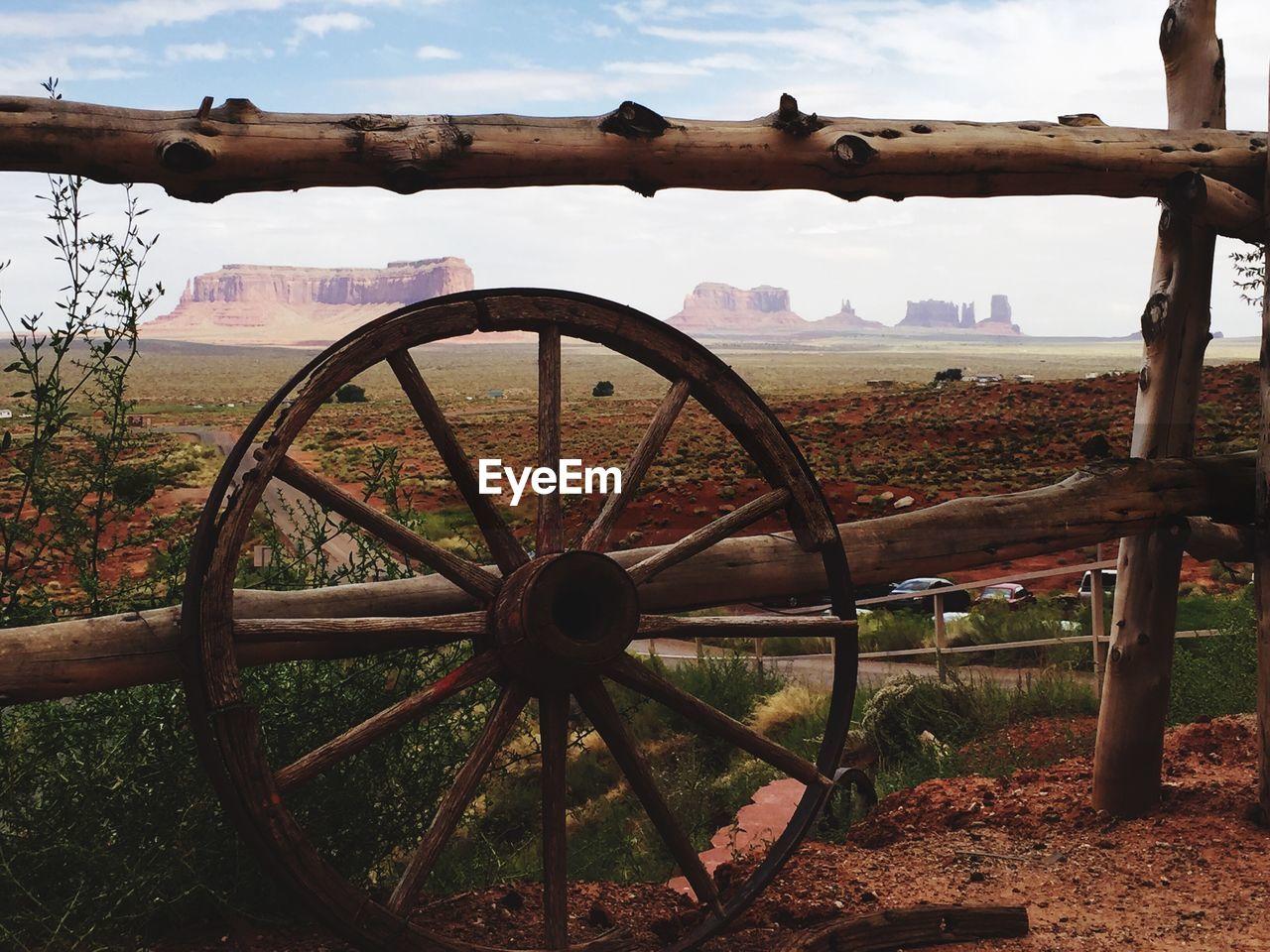 Wheel By Wooden Fence On Field Against Sky