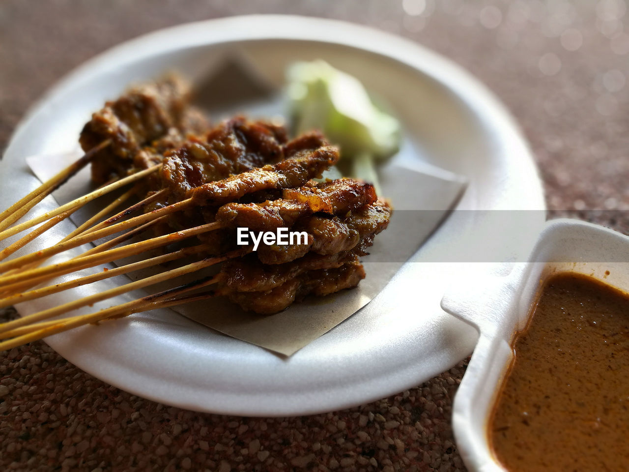 Close-up of satay by sauce on table
