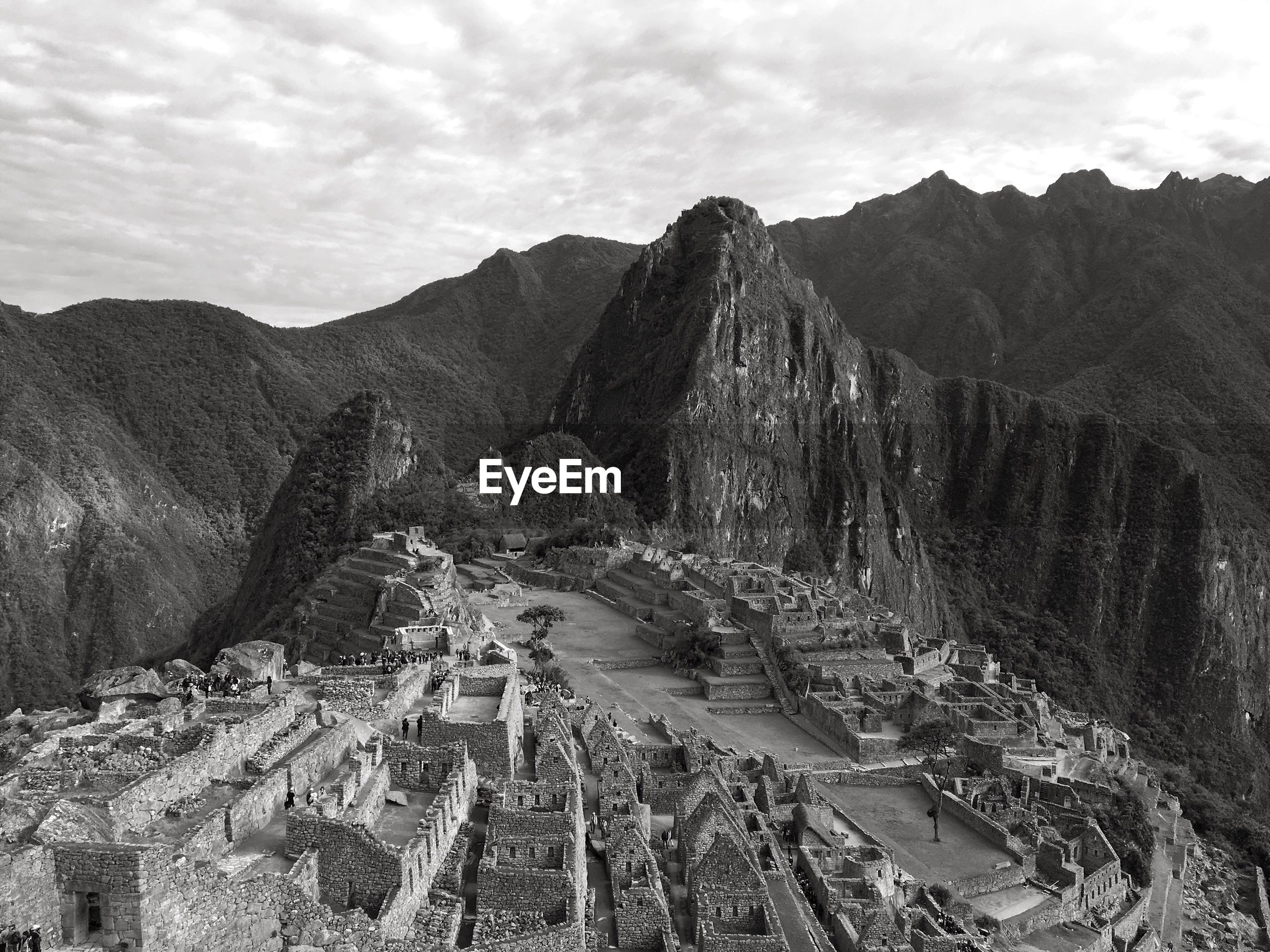 High angle view of old ruins by mountains against cloudy sky