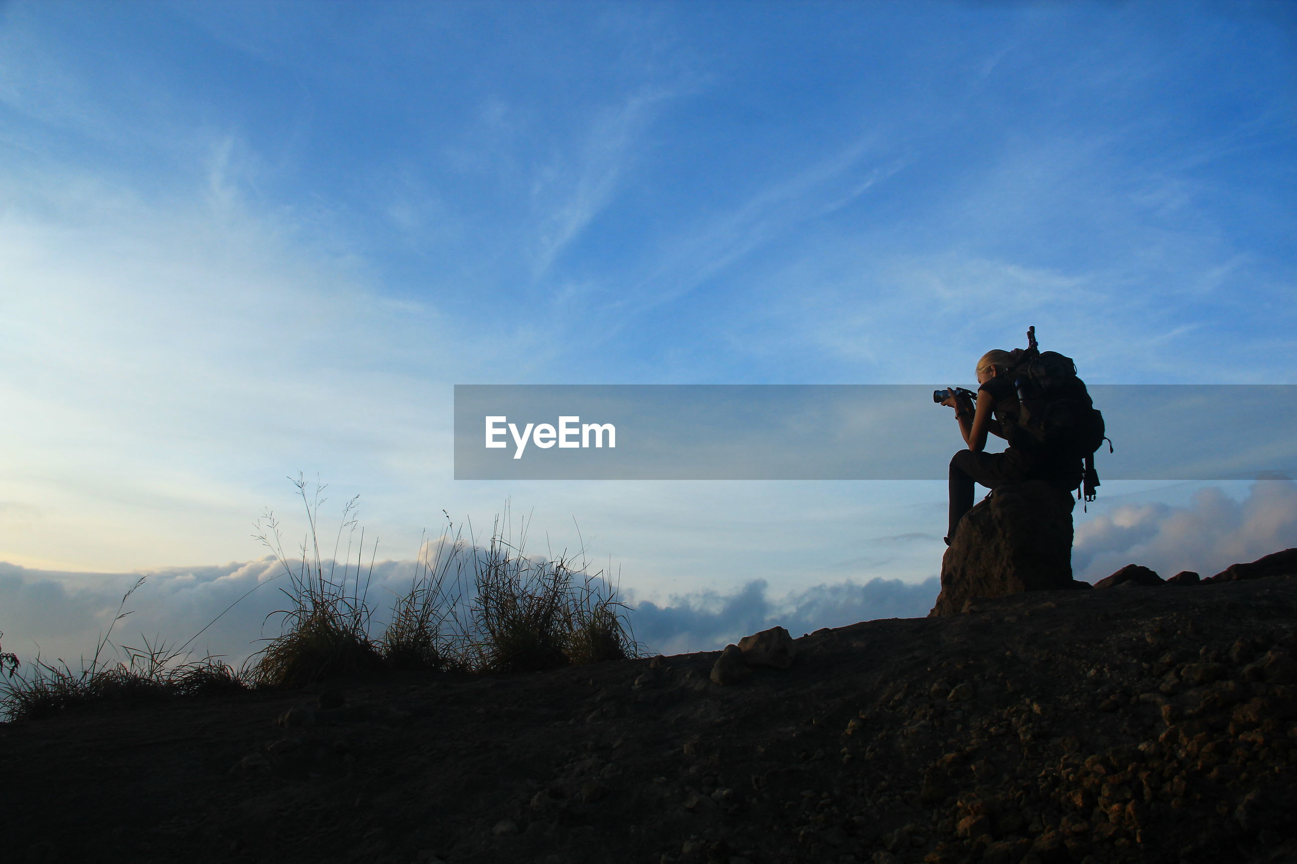 Low angle view of man photographing while sitting on rock against sky
