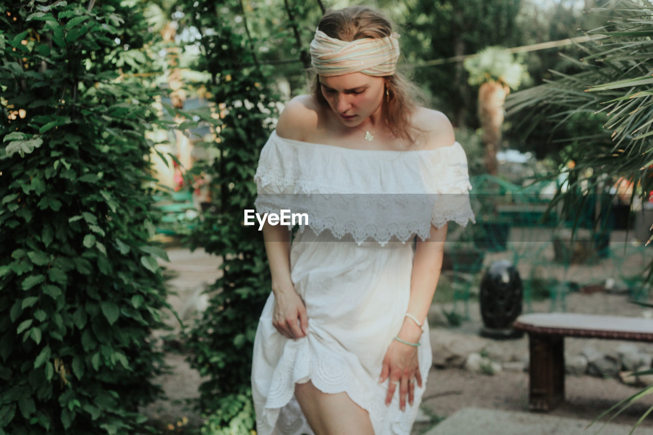one person, real people, young adult, young women, standing, leisure activity, tree, focus on foreground, hair, lifestyles, front view, plant, day, three quarter length, women, white color, casual clothing, hairstyle, fashion, beautiful woman, outdoors