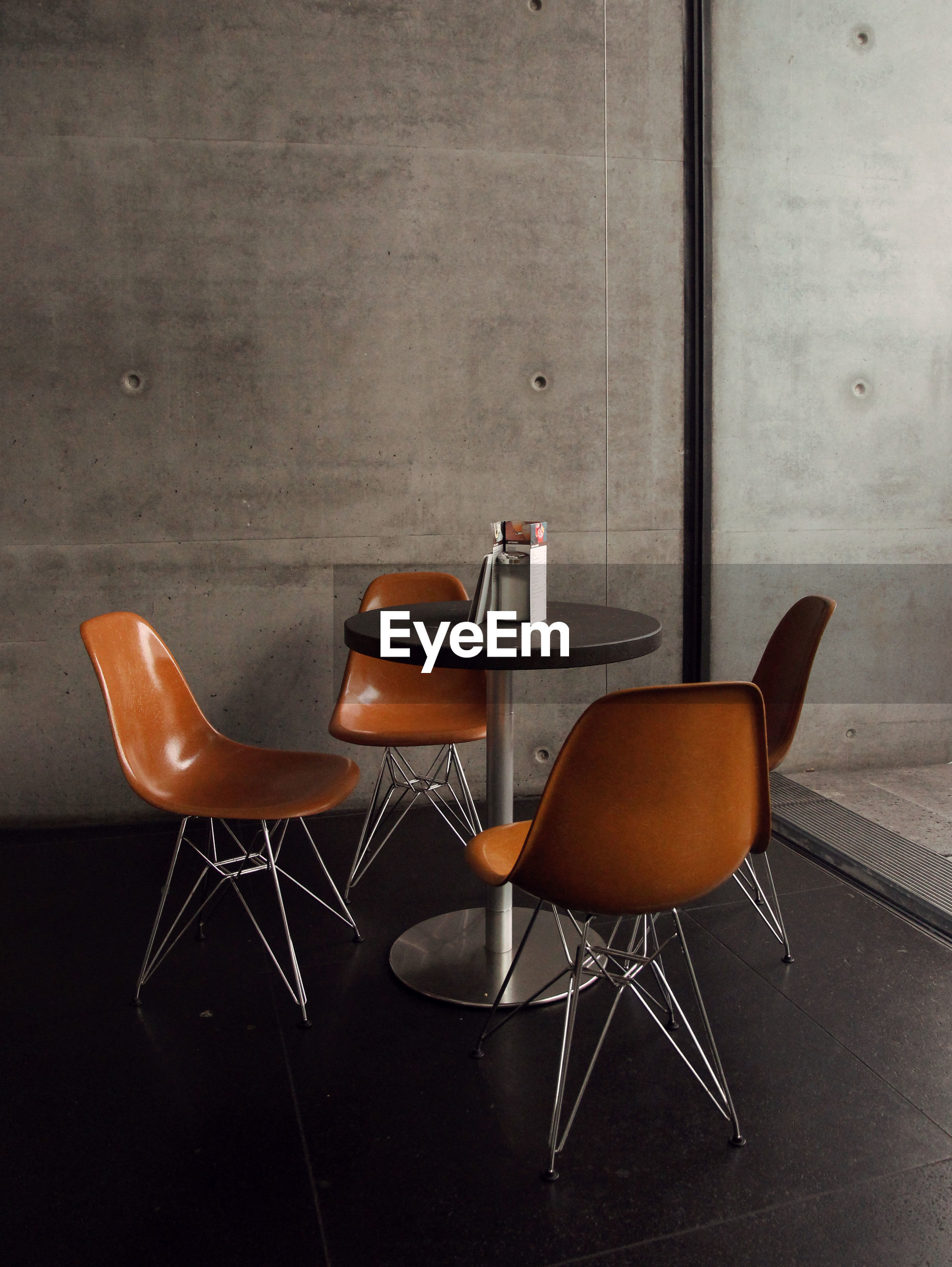EMPTY CHAIRS AND TABLE ON WALL
