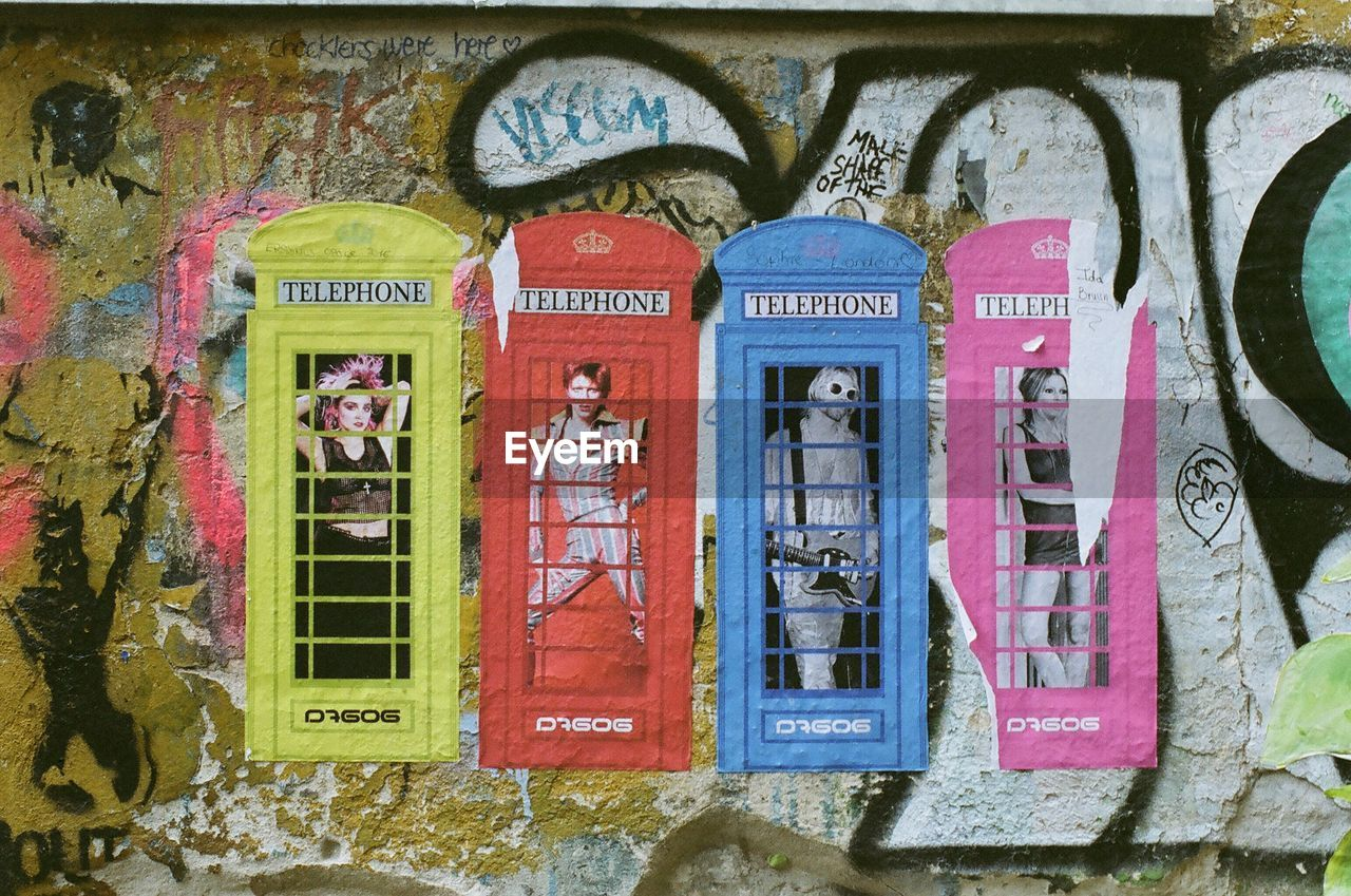 graffiti, text, communication, architecture, built structure, no people, day, outdoors, building exterior, telephone booth, multi colored, pay phone, close-up