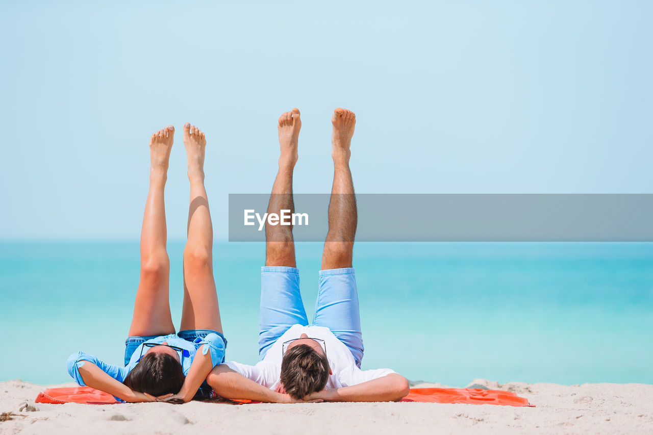 Couple with feet up while lying on beach