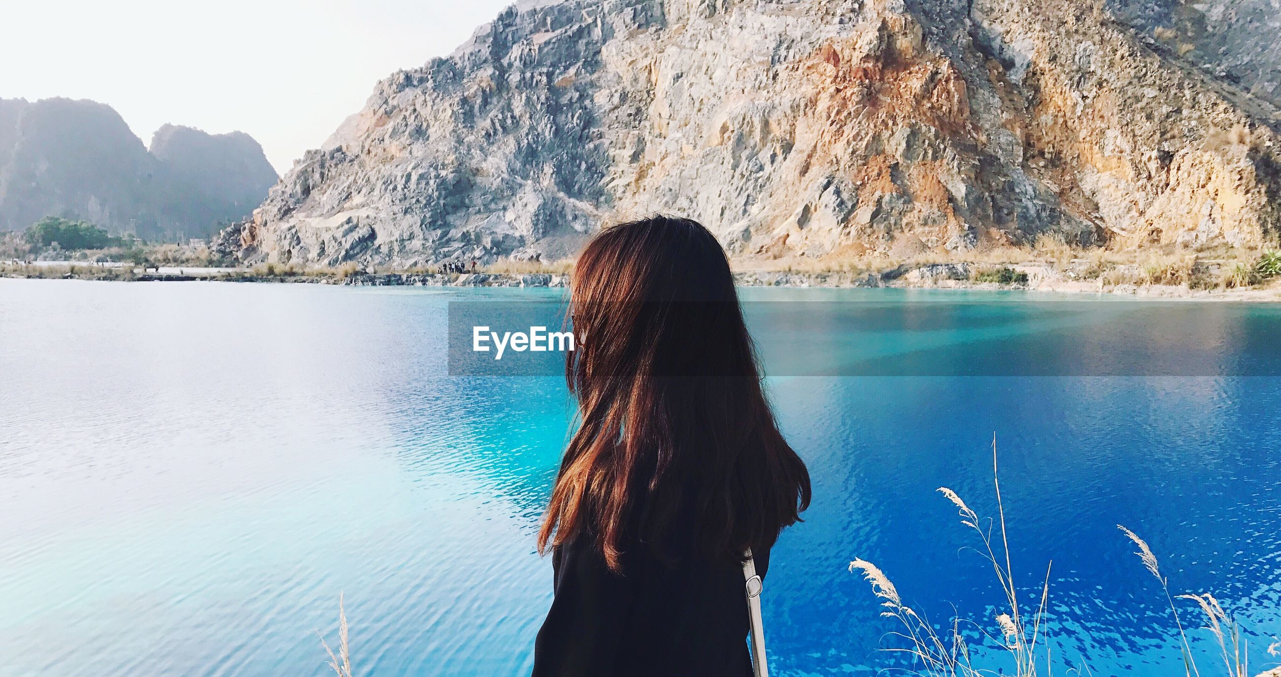Side view of woman looking at lake against mountain