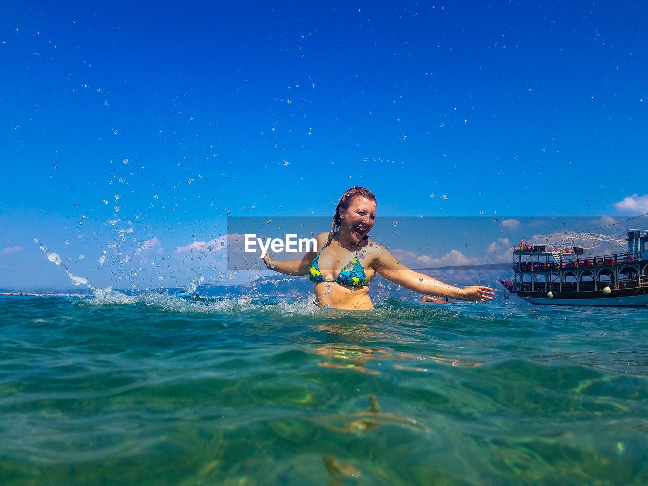 Cheerful woman swimming in sea against blue sky during sunny day