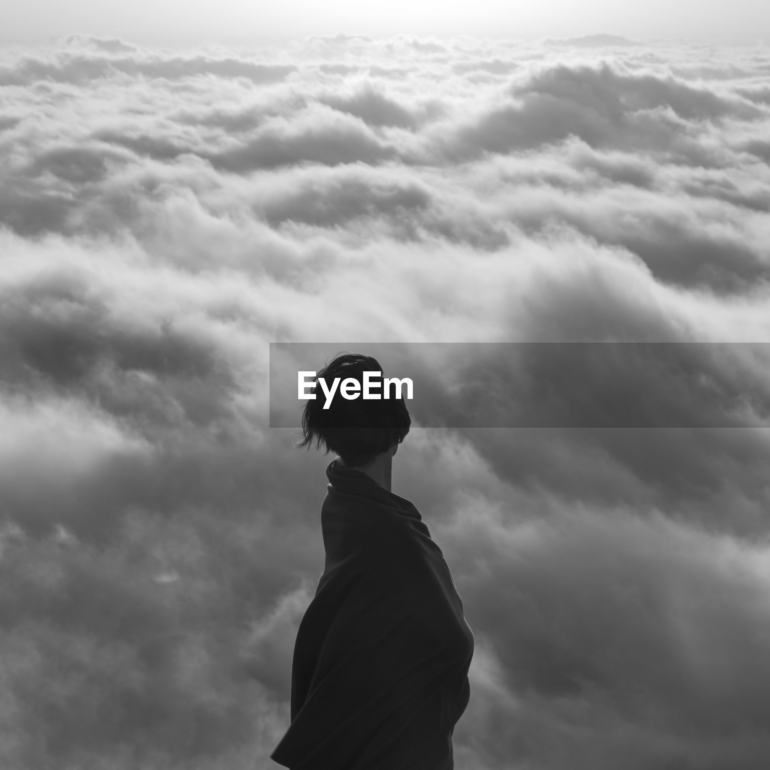 Side view of woman standing against cloudy sky