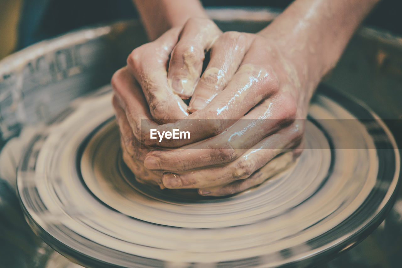 Master potter folded together hands sculpts a clay product on a potter's wheel.