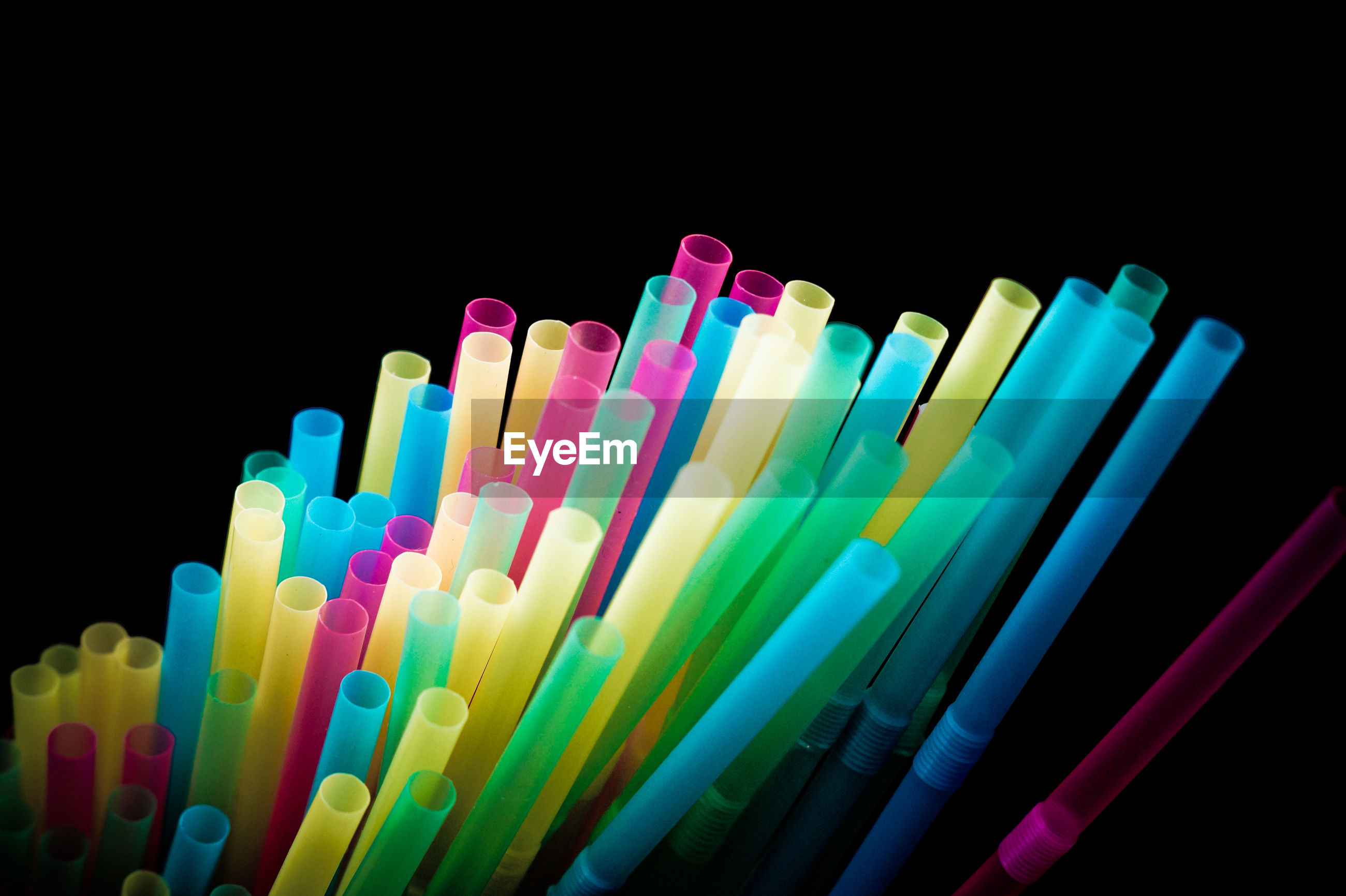 Close-up of colorful drinking straws against black background
