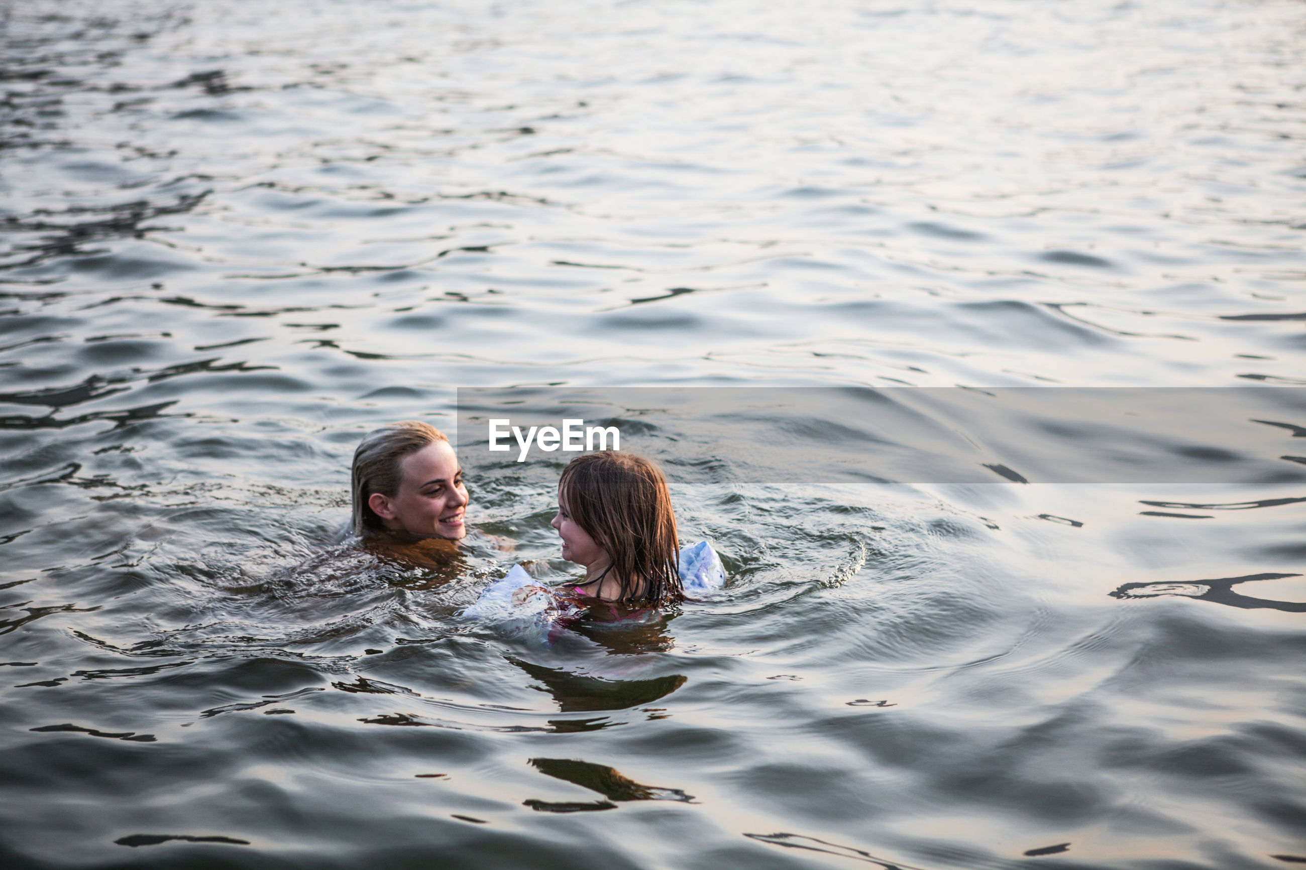 Mother and daughter swimming in sea