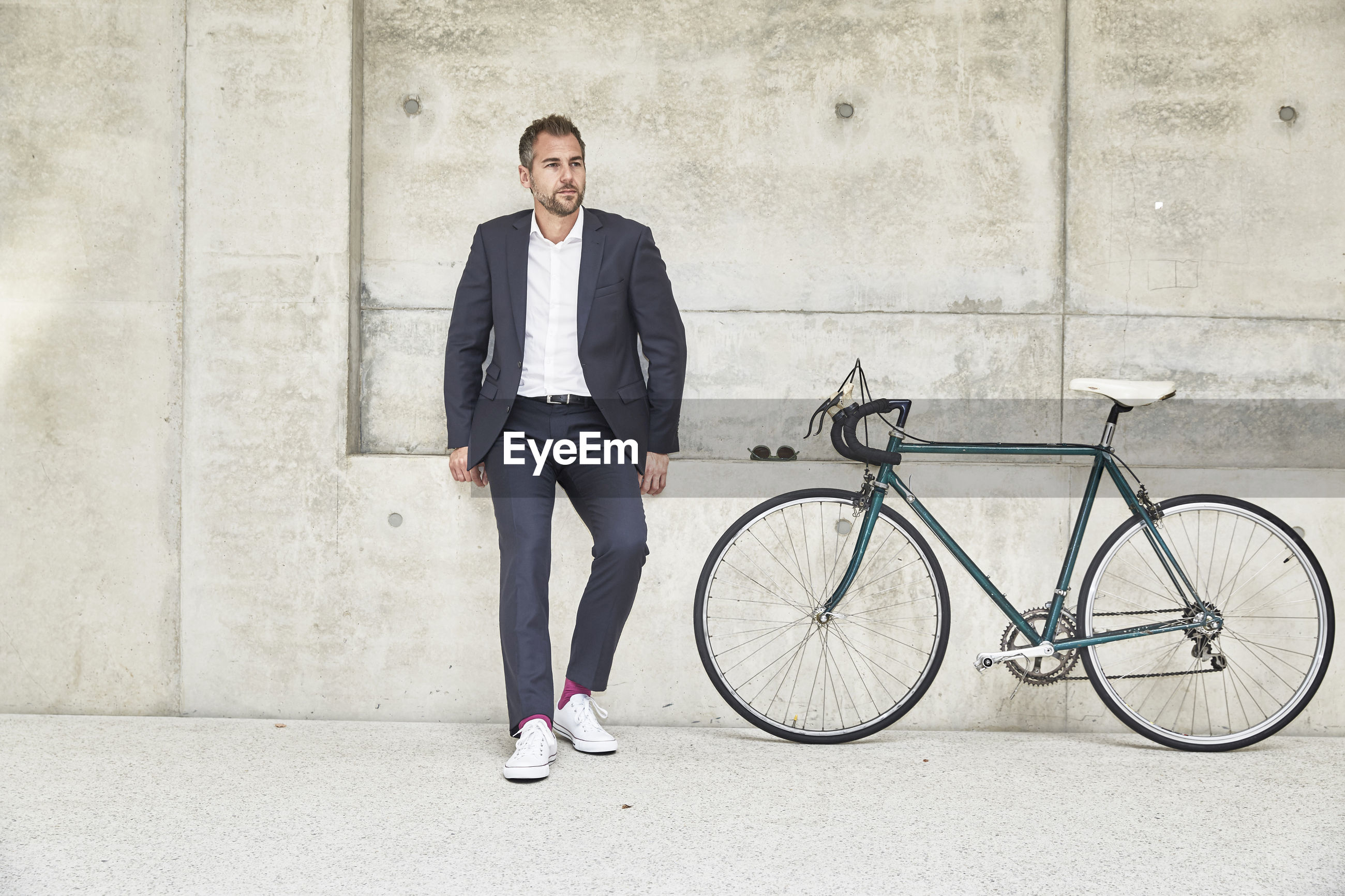 FULL LENGTH PORTRAIT OF A YOUNG MAN WITH BICYCLE AGAINST WALL
