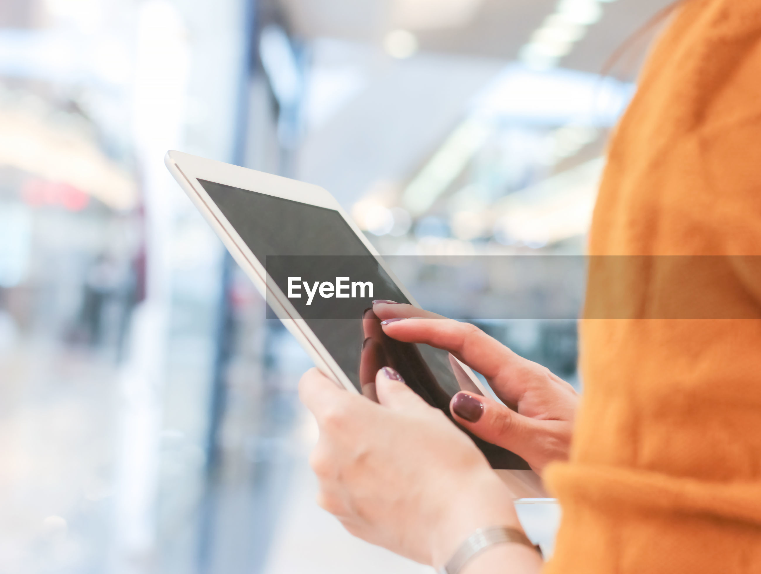 Close-up of woman using digital tablet in illuminated store