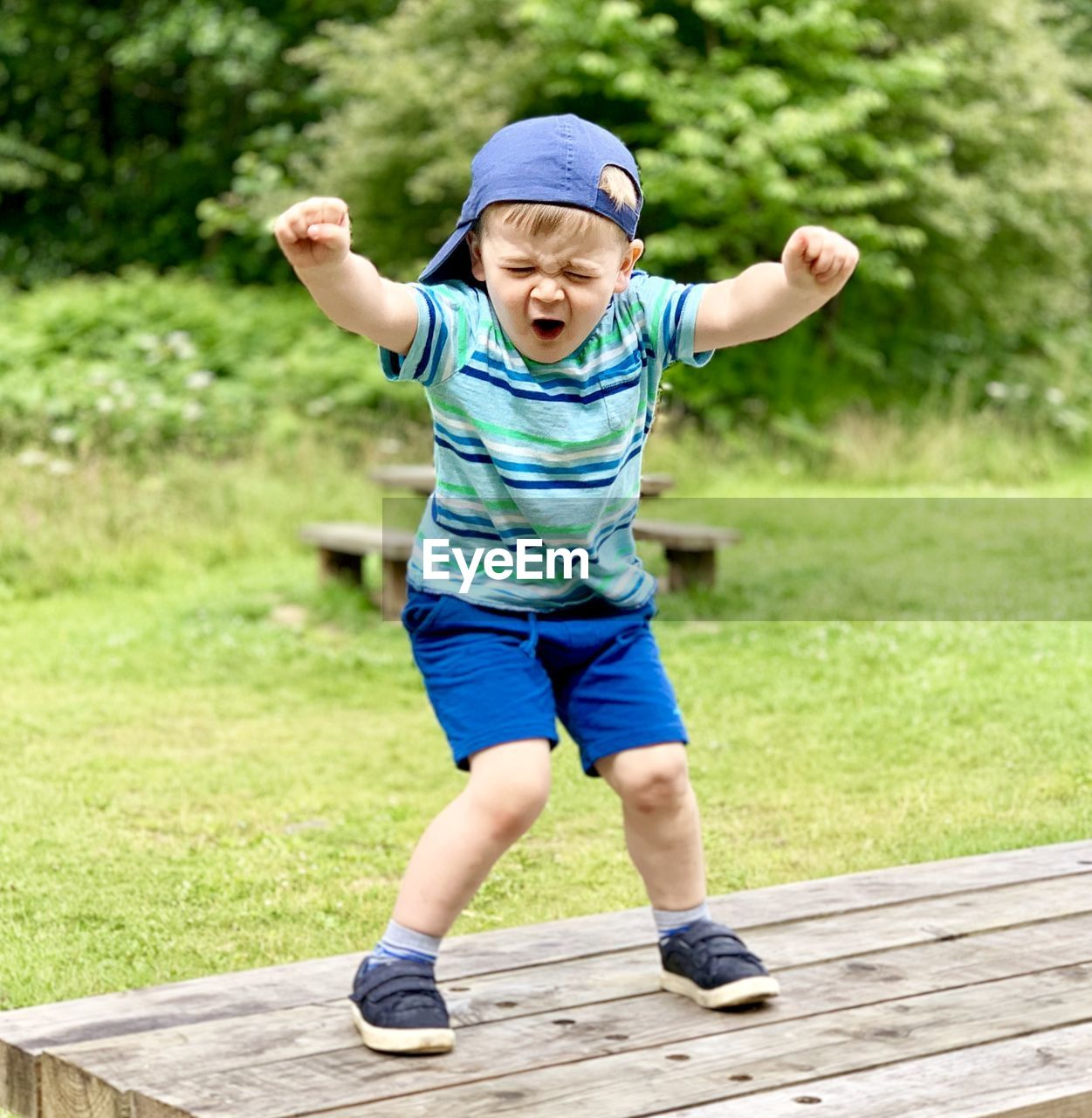 Full length of cheerful boy standing on table