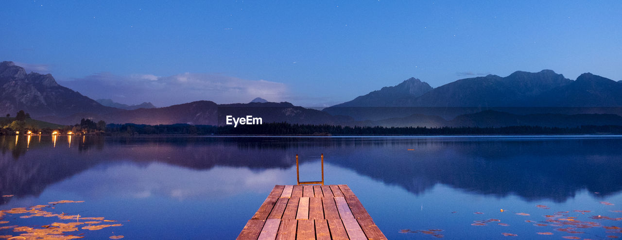 water, sky, lake, reflection, scenics - nature, beauty in nature, mountain, tranquility, nature, wood - material, tranquil scene, pier, non-urban scene, mountain range, no people, idyllic, standing water, nautical vessel, jetty, outdoors
