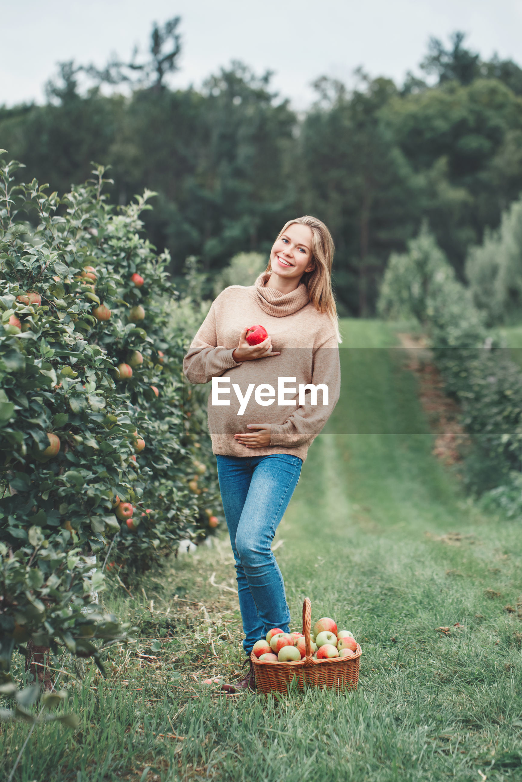 Portrait of smiling pregnant woman holding apple while standing by basket and trees