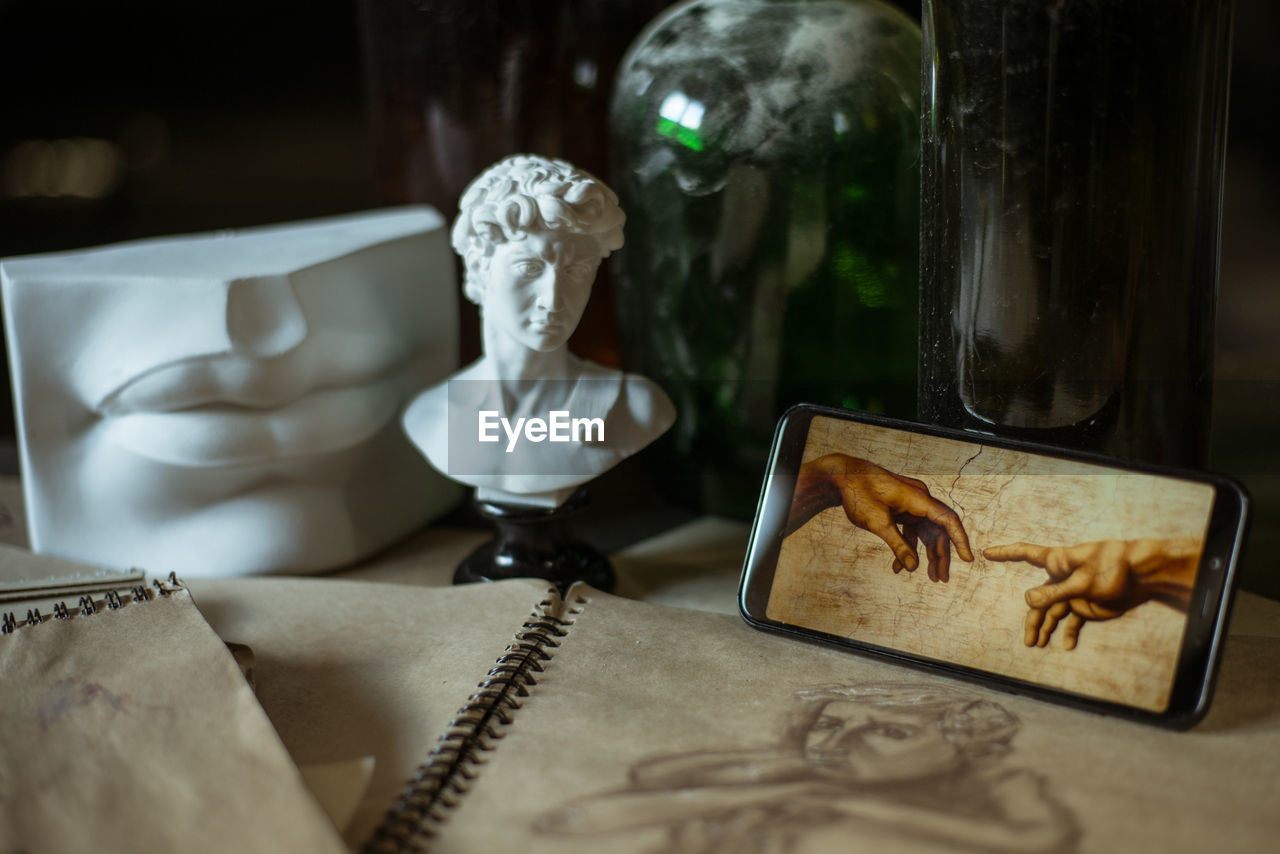 representation, human representation, no people, still life, table, indoors, art and craft, creativity, focus on foreground, male likeness, publication, close-up, communication, technology, book, sculpture, figurine, glass - material, day