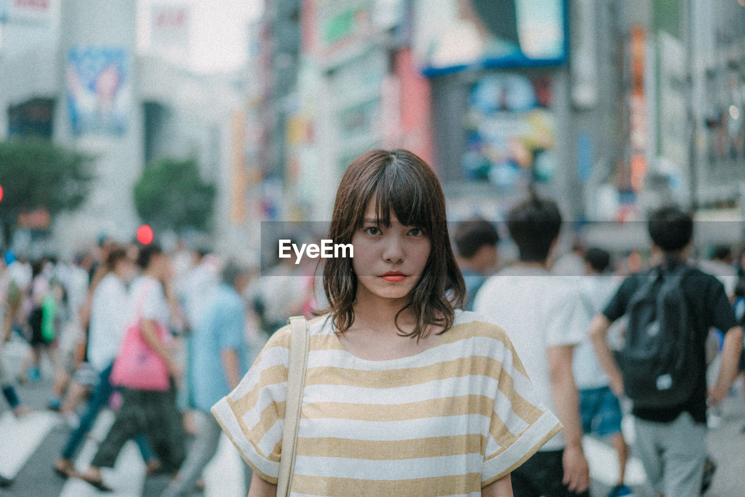 focus on foreground, real people, city, casual clothing, lifestyles, incidental people, standing, portrait, one person, front view, leisure activity, women, looking at camera, street, young adult, waist up, young women, architecture, hairstyle, beautiful woman
